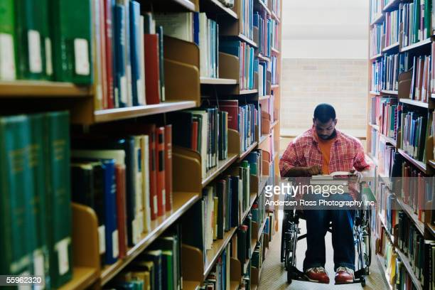 Male college student in wheelchair at library