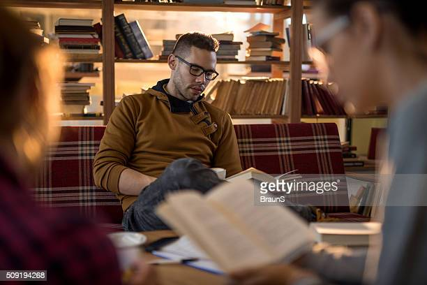 Male college student reading a book in a library.