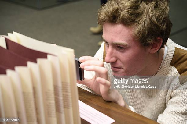 Male college student taking a picture with his phone of an artifact at in the Special Collections brand of the Johns Hopkins University Sheridan...