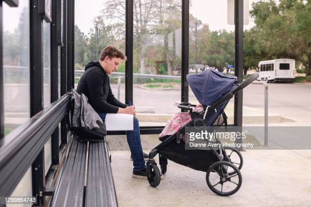 male college student with baby stroller at bus stop - thousand oaks stock pictures, royalty-free photos & images