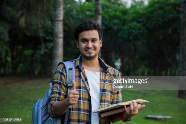 male college student with books outdoors - stock image - man holding book stock pictures, royalty-free photos & images