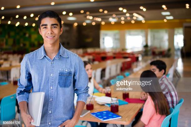 Male college student with laptop looking at camera