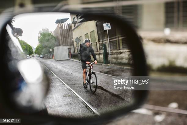 male commuter riding bicycle on wet street seen through side-view mirror of car - side view mirror stock photos and pictures