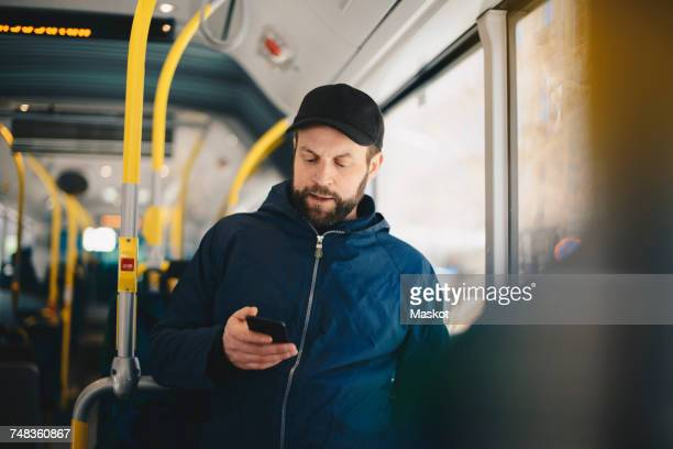 male commuter using mobile phone while traveling in bus on sunny day - transporte público imagens e fotografias de stock