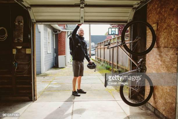 male commuter with backpack closing garage door - autobergplaats stockfoto's en -beelden