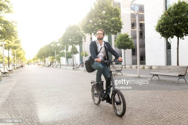 male commuter with electric bike in mitte - city stock pictures, royalty-free photos & images