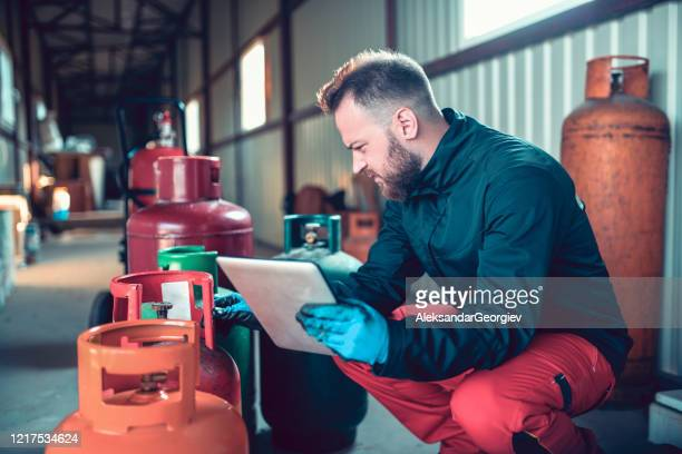 male comparing gas cylinders serial number with his database on digital tablet - storage tank stock pictures, royalty-free photos & images