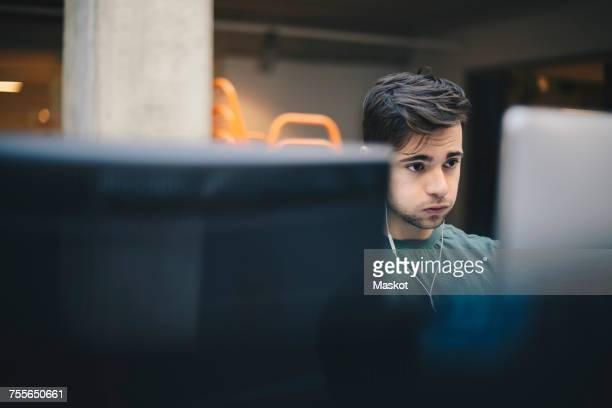 Male computer programmer puffing cheeks while using desktop PC in office
