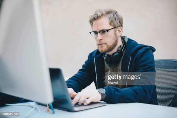 Male computer programmer using laptop at desk in office