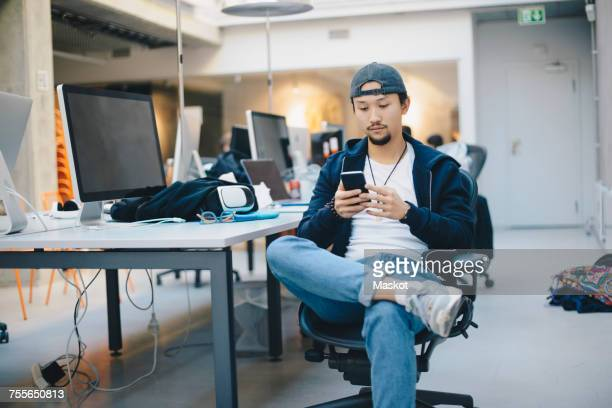 male computer programmer using smart phone while sitting on chair in office - ジーンズ ストックフォトと画像