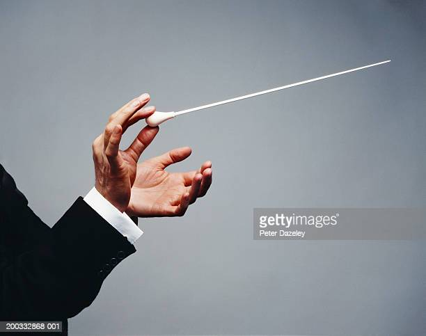 male conductor holding baton, close-up of hands - maestro stock photos and pictures
