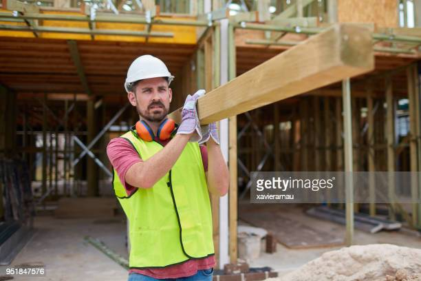 male construction worker carrying wood at site - carrying stock pictures, royalty-free photos & images