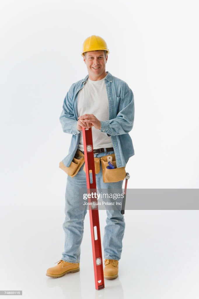 Male construction worker holding level : Stock Photo