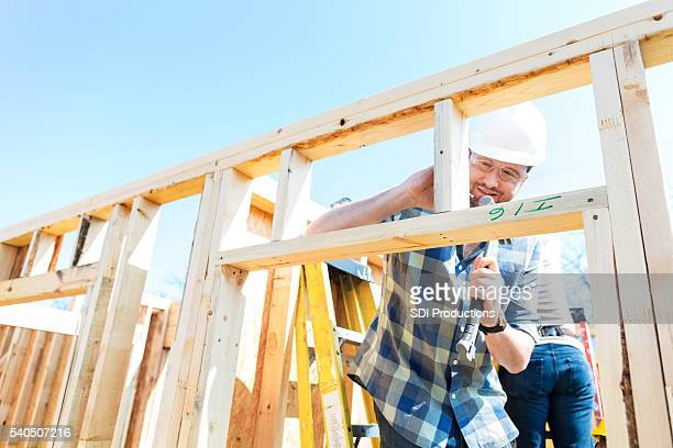 male construction worker uses hammer at job site - construction material stock pictures, royalty-free photos & images