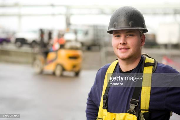 Male construction worker wearing black hard hat and overalls