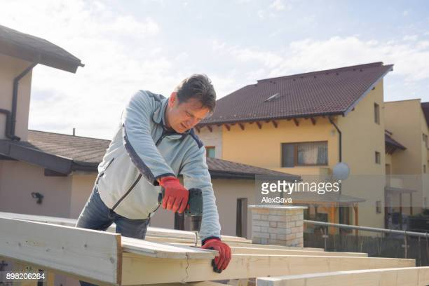 Male constructor drilling wooden chalet roof
