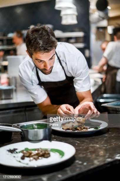 cuoco maschio prepara cibo in cucina commerciale - chef foto e immagini stock