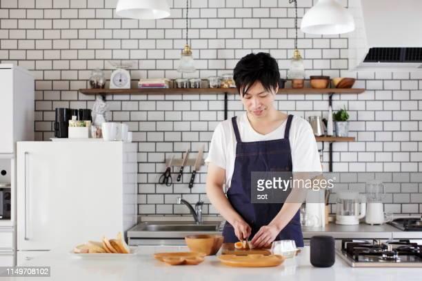 キッチンでスマートスピーカーを使用して、男性の調理 - 夫 ストックフォトと画像
