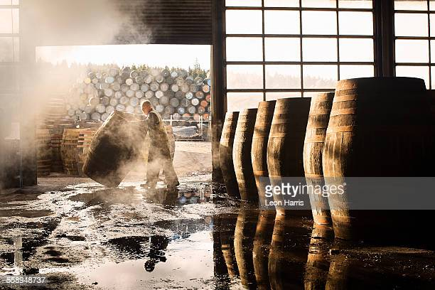 male cooper working in cooperage with whisky casks - scotland stock pictures, royalty-free photos & images