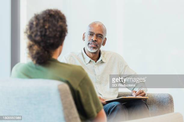 male counselor talks with female soldier during session - army stock pictures, royalty-free photos & images