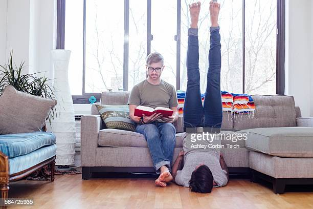 male couple at home, mid adult male reading whilst partner does shoulder stand - mid adult stock pictures, royalty-free photos & images