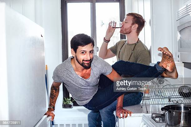 Male couple at home, mid adult man drinking whilst his partner balances on kitchen appliances