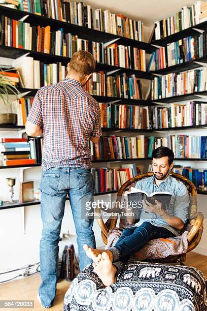 Male couple at home, reading and looking at books on bookshelf
