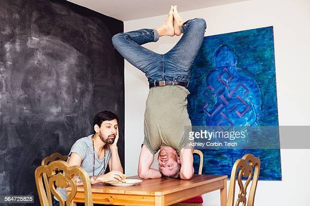 Male couple at home, young man eating meal whilst his partner does headstand on table