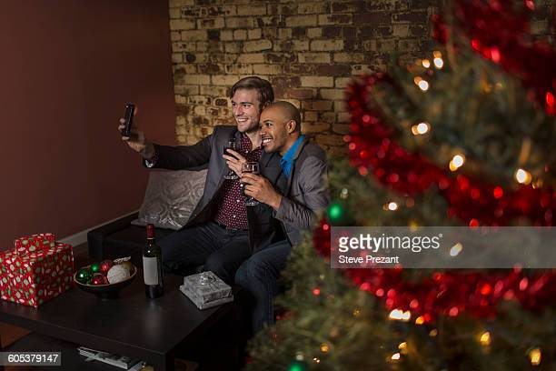 Male couple celebrating Christmas together, sitting on sofa, taking self portrait using smartphone
