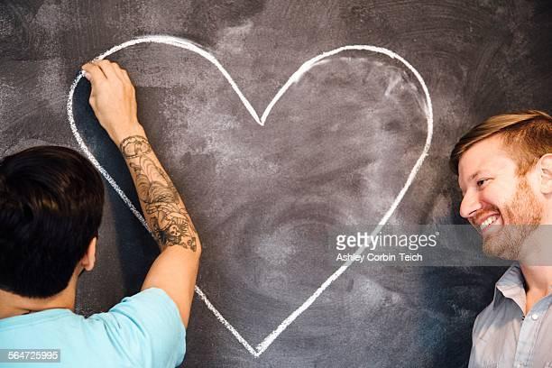 Male couple drawing heart on blackboard