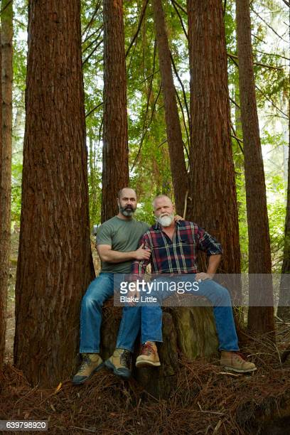 Male Couple in Forest sitting on stump