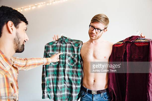 Male couple, mid adult man asking for help choosing shirt