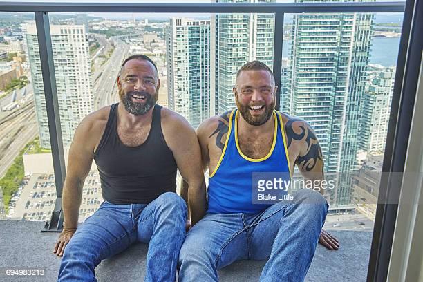 Male Couple on Balcony City View Portrait