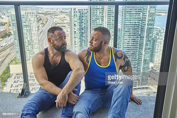 Male Couple on Balcony City View Profile