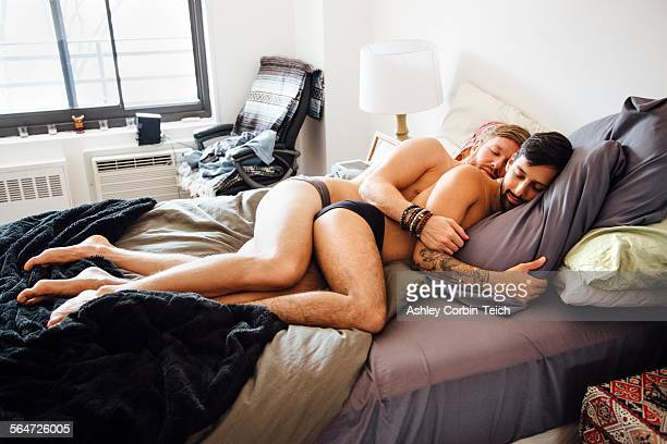 male couple, partially dressed, lying together on bed, sleeping - abbracciarsi a letto foto e immagini stock