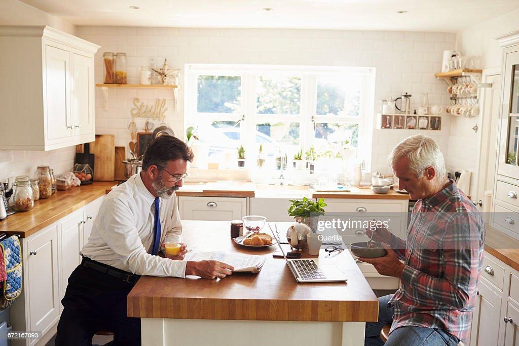 Male Couple Sitting At Kitchen Island Before Work Close Up Stock