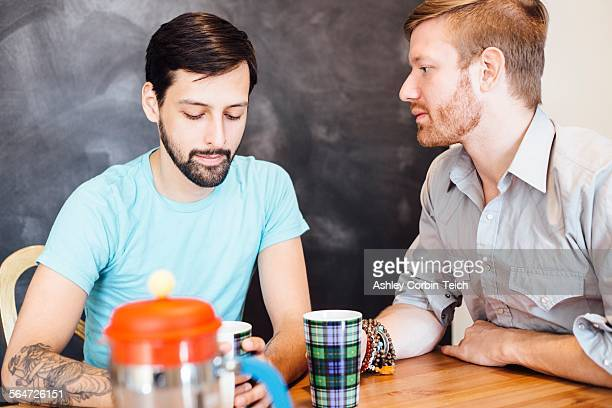 Male couple sitting at table, drinking coffee