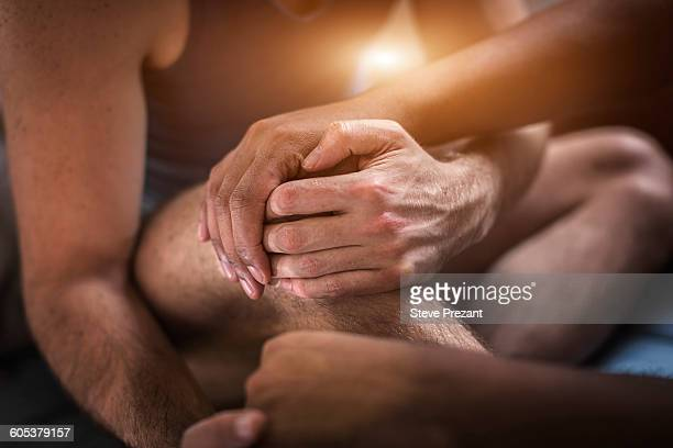 Male couple sitting together, holding hands, mid section