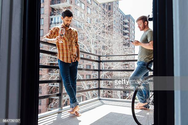 Male couple standing on balcony, standing away from each other, drinking wine and looking at smartphone