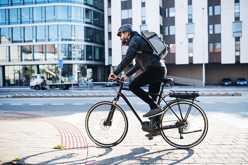 Male courier with bicycle delivering packages in city. Copy space. 1132953037