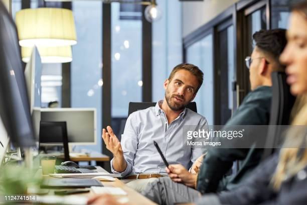 male coworkers discussing during meeting in office - colletti bianchi foto e immagini stock