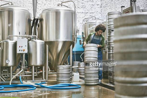 male craft brewery worker stacking kegs for washing - brewery stock pictures, royalty-free photos & images