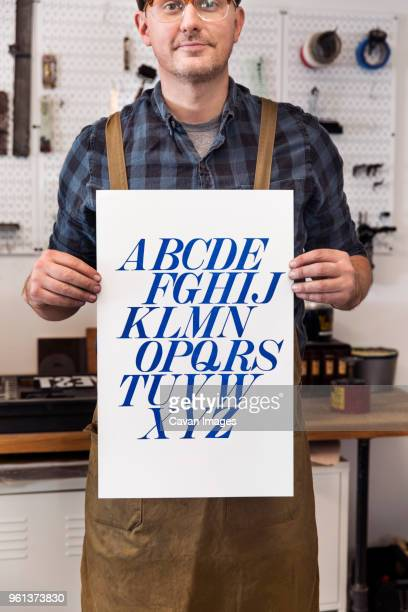 Male craftsperson holding poster and standing in printing press