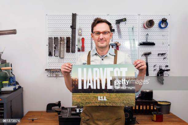 Male craftsperson holding poster and standing in workshop