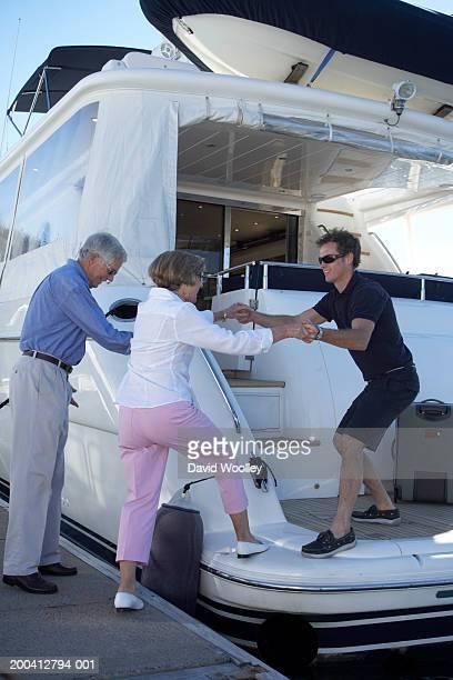 Hombre ayudando a senior Mujer miembro de la tripulación en yate en