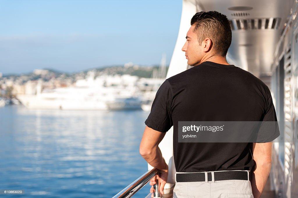 Male crew member looking from yacht boat : Foto de stock