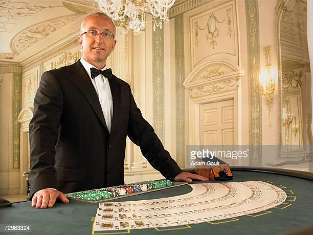 Male croupier at Blackjack table in casino, portrait