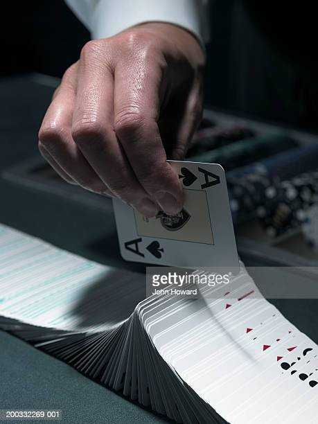 Male croupier extravagantly shuffling cards at table, close-up