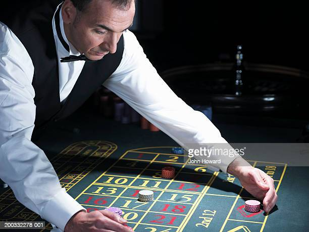 Male croupier gathering bets at roulette table