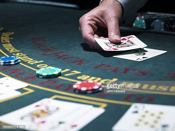 male croupier holding card at blackjack table, close-up - gambling stock pictures, royalty-free photos & images